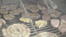 The cook turns the meat during grilling Footage
