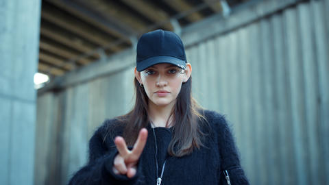 Girl showing v sign on city street. Fashion woman showing v gesture outdoors Live Action