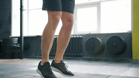 Tilt-up of sporty man jumping with skipping rope in gym working out alone Live Action
