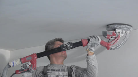 Dirty plasterer man polish ceiling with sanding machine. House renovation Live Action