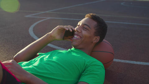 Athlete chatting on phone on basketball court GIF