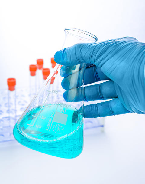 Medical analyst with conicial flask with blue liquid Fotografía