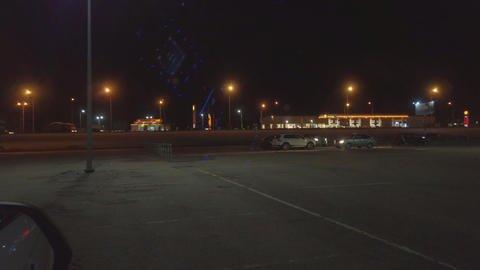 Empty car Park at night against the background of the road on which cars are Acción en vivo