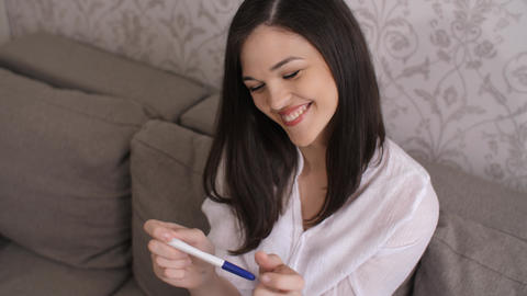 Cheerful woman looks at pregnancy test ライブ動画