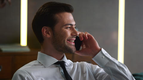 Portrait of happy businessman talking on mobile phone at remote workplace Live Action
