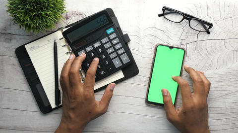 Top view of man hand using smart phone and calculator on table Live-Action