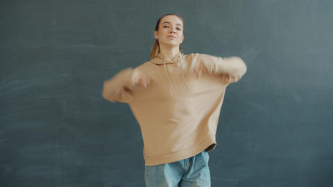 Portrait of joyful girl dancing in modern dance studio alone moving body and Live Action
