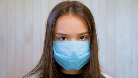Portrait of beautiful brunette teen girl in medical protective mask over light ライブ動画