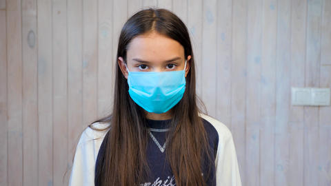 Teenage girl wearing medical protective facemask looking at camera. Covid-19 ライブ動画