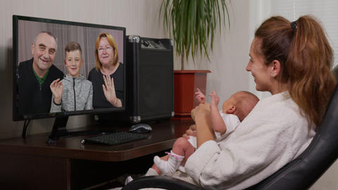 mother and baby having video chat using PC waving at newborn infant enjoying Live-Action