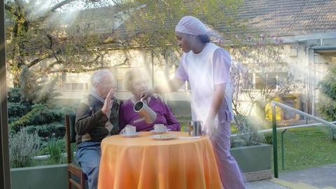 Slow motion of elderly retired couple having breakfast outdoor served by nurse GIF