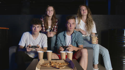 Friends console party. Two male friends winning in video game, sitting on couch Live Action