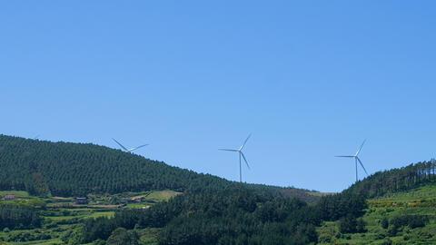 Rotating wind turbines on green hill, clean energy farm, eco technology ライブ動画