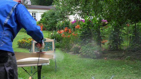 Guy performs work in yard as a hobby. Uses grinding tools, dust mask and glasses GIF