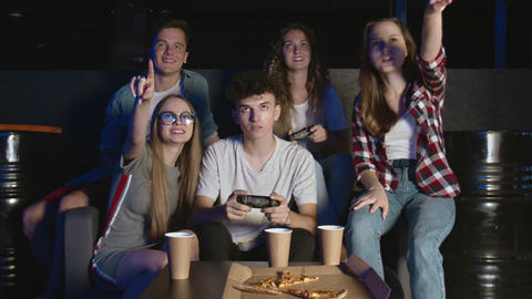 Happy group of friends playing video games at home. Man and woman are playing GIF