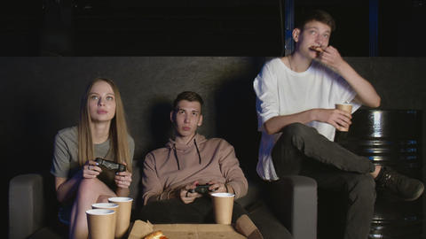 Cheerful company plays in the console game, girl against boy. Eats pizza GIF