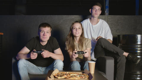 Friends play on the game console. They are sitting on the couch and holding the GIF
