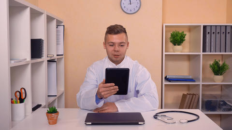 man wearing white coat looking on screen computer and speaking ライブ動画