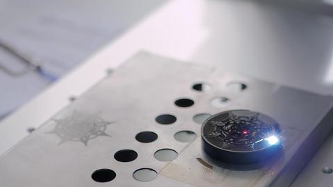 Laser engraving machine burning sign of star on circular plastic workpiece Live Action