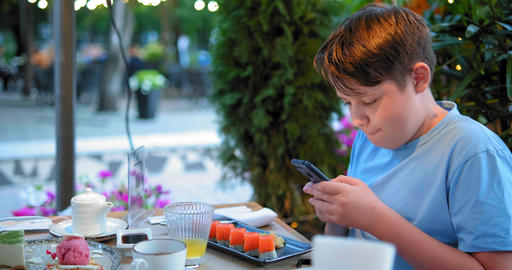 concentrated schoolboy makes photo of sushi in restaurant GIF