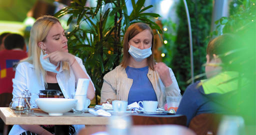 ladies take off blue face masks sitting at restaurant table GIF