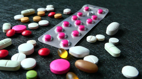 close up of colorful pills spilling on black background ライブ動画