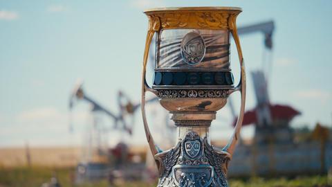 shiny cup with Yuri Gagarin against oil extracting equipment Acción en vivo