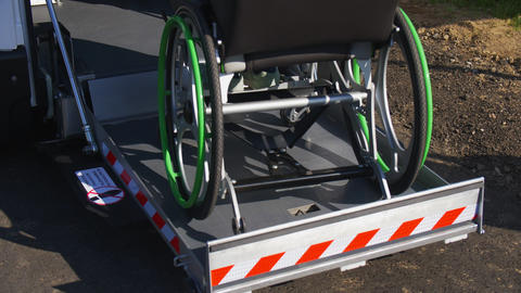 person in wheelchair uses automatic ramp to get inside van GIF