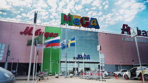 facade of Mega supermarket with flags and walking people GIF
