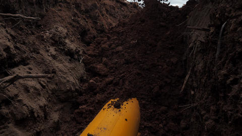 pouring dirt onto yellow pipe covered with protective casing Live Action