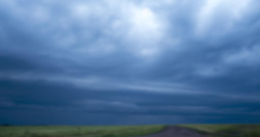 blurred blue stormy clouds with lightnings float in sky over fields GIF