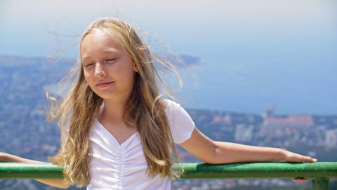 Smiling girl teenager with hair on wind standing on observation deck on mountain ライブ動画
