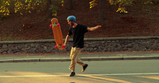 Trick on a longboard. The guy scrolls a skateboard at sunset Live Action