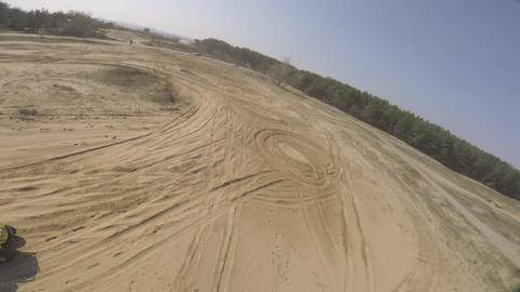 FPV drone is flying around a man on an ATV driving in the dust Live Action