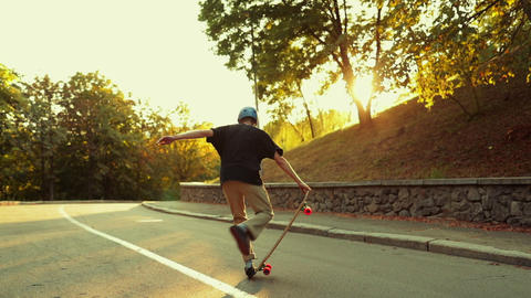 The guy spins on a longboard at sunset Live Action