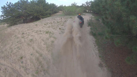FPV drone is following a man on an ATV driving off-road, high speed Live Action