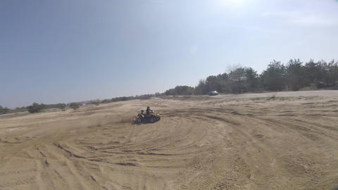 Lots of dust is bursting from under the wheels of an ATV, freestyle drone Live Action