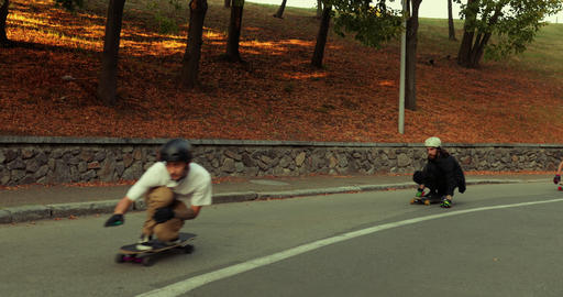 A group of guys ride a longboard around the evening city. Slow motion video Live Action