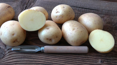 Potatoes on the wood board. Fresh potato on rustic background GIF