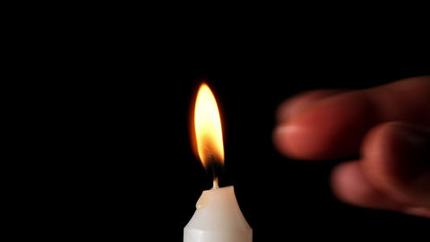 burning white wax candle on a black background, hand extinguishes flame with fingers Acción en vivo