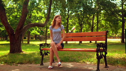 woman waiting for friend in park Live Action