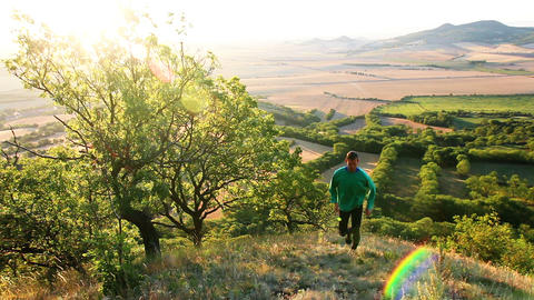 Young man runing up to hill in Czech central mountain valley at sunrise. Outdoor landscape GIF