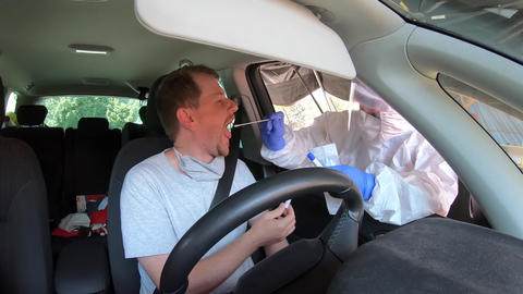 Man in car having oral swab PCR test for possible infection GIF