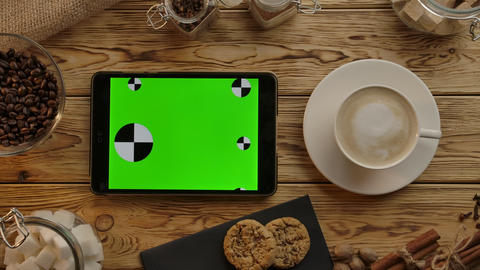 Digital tablet with green screen lying horizontally on wood desk. Eat,drink,work Live Action