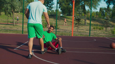 Streetball player helping opponent to stand up Acción en vivo