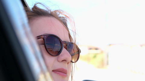 Young beautiful woman in sunglasses sitting in car looking out of window peacefully and enjoys the GIF