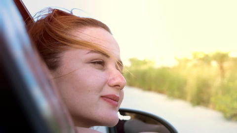 Happy young beautiful woman sitting in car looking out of window and enjoying, having fun during a GIF