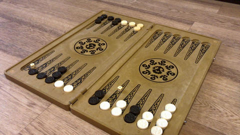 Detail of a backgammon game with two dice close up. Male hands rolling two dice Live Action