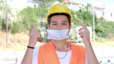 Portrait of male engineer or worker with yellow helmet wearing face mask looking at camera and GIF