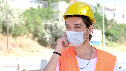 Portrait of male engineer or worker with medical mask and yellow helmet talking on the mobile phone GIF